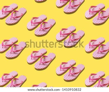 Creative beach slippers pattern on yellow background. Summer minimal concept.