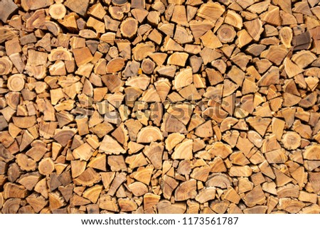 Creative brown background of neatly stacked firewood. Brown texture of natural wood #1173561787