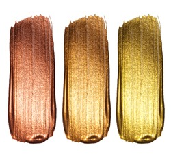 Creative brushstrokes of gold paint isolated on a white background. Gold paint texture.Acrylic gold paint. Smears of cosmetics, blush, highlighter, eye shadow, lipstick.