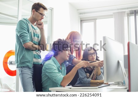 Creative business colleagues discussing over computer in office