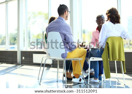 Creative business people meeting in circle of chairs
