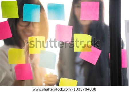 Creative business people putting their ideas at sticky notes on window during a presentation in meeting room. Smiling partners brainstorm concept. Setup studio shooting. #1033784038