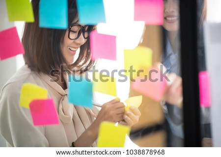 Creative business people putting their ideas at sticky notes on window during a presentation in meeting room. Smiling partners brainstorm concept. Setup studio shooting.