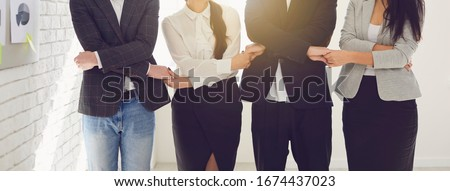 Creative business people team holding hands while standing indoors.