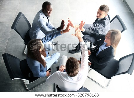 Creative business team putting hands together at the office