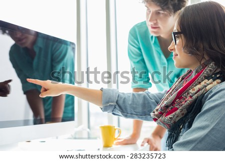 Creative businesswoman showing something to colleague on desktop computer in office