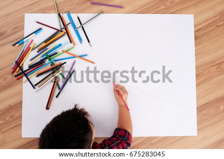 Creative child drawing with colored pencils on big white sheet, view from above