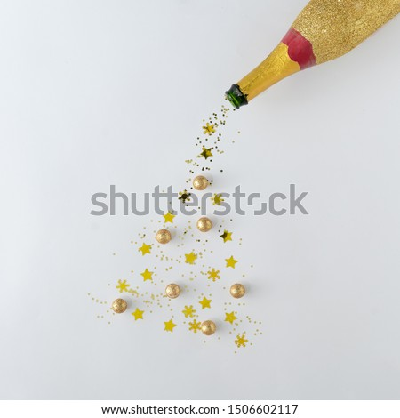 Creative Chrismas or New Year background. Champagne bottle with gold glitter Christmas tree. Minimal flat layt concept.