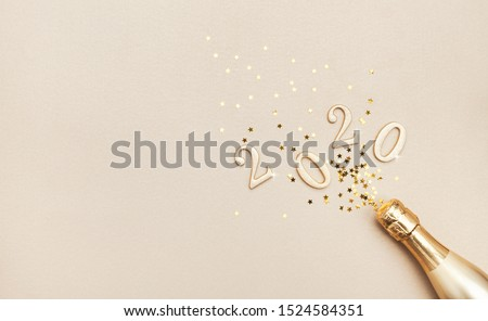 Creative Christmas and New Year composition with golden champagne bottle, confetti stars and 2020 numbers. Flat lay.
