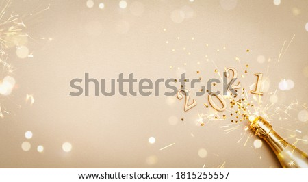 Creative Christmas and New Year greeting card with golden champagne bottle, confetti stars and 2021 numbers. Flat lay. Banner format.