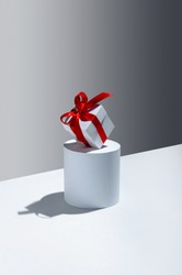 Creative Christmas Concept. White Gift Box with Red Ribbon on Stand