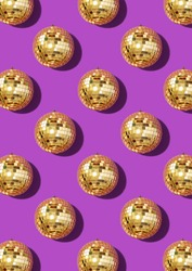 Creative Christmas pattern. Shiny gold disco balls over violet background. Flat lay, top view. New year baubles, star sparkles. Party time. Cristmas greeting card.