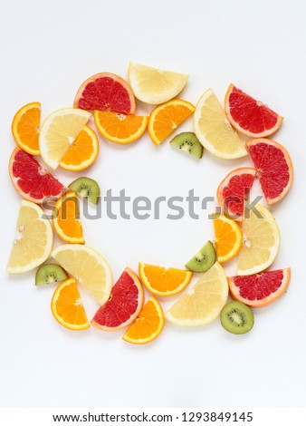 Creative circle arrangement of sliced fruits - kiwi, orange and grapefruits. Flat lay with copy space #1293849145