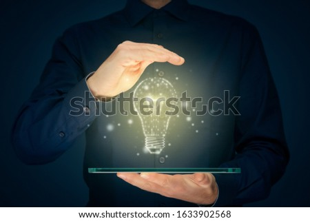 Creative company give you their creativity and ideas. Hands with tablet and graphics light bulb - symbols of idea, creative thinking, innovations and intelligence.