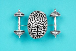 Creative composition made of a steel copy of a human brain lifting dumbbells. The concept of brain exercises to strengthen the mind.