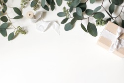 Creative composition made of green berry Eucalyptus populues leaves and branches, gift box and wooden spool with silk ribbon isolated on white background. Wedding styled photo,  flat lay, top view.