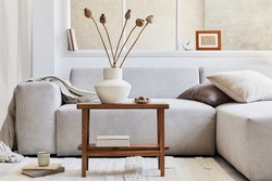 Creative composition of stylish living room interior with grey corner sofa, window, wooden coffee table, vase with dried flowers and personal accessories. Beige neutral colors. Template.