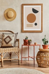 Creative composition of stylish living room interior with mock up poster frame, rattan armchair, coffee table, cacti and personal accessories. Plant love and nature concept. Template.