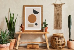 Creative composition of stylish living room interior with mock up poster frame, wooden bench, rattan basket, cacti and boho accessories. Plant love and nature concept. Template.