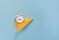 Creative composition Time flies. A small white alarm clock on a yellow paper on a paper blue background. Top view. Flat lay.