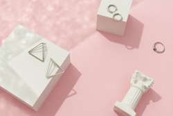Creative composition with silver jewelry set on pink background. Trendy accessories in minimalist style