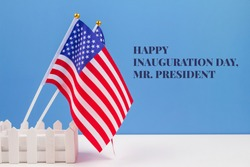 Creative composition with USA flags on white table with blue wall background, copyspace for text. Happy Inauguration Day wishes 2021 concept
