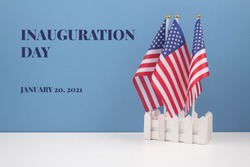 Creative composition with USA flags on white table with blue wall background, copyspace for text. Inauguration Day 2021 concept