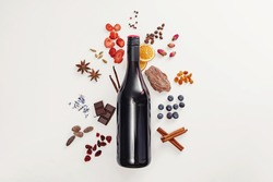 Creative composition with wine bottle and possible flavor components of red wine - berries, spices and other. Flat lay composition, wine tasting concept.