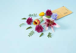 Creative concept of post delivery of the shipment full of fresh colorful flowers. Package of a bouquet of flowers on pastel blue background.