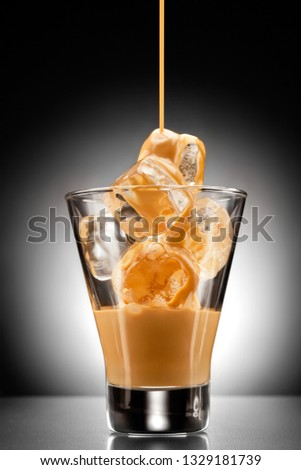 Creative concept photo of alcohol spirits drink beverage cocktail Irish cream liqueur pouring into a glass full of ice #1329181739