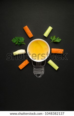 Creative concept photo of plate with vegetables arranged as electric bulb on black background.