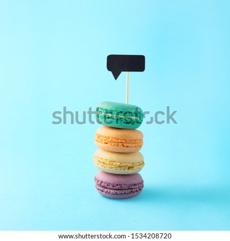 Creative concept still life food diet health photo of macarons macaroons pastry almond sweet confectionary with message cloud notification on blue background.
