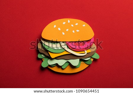 Creative conceptual art minimal still life. Paper craft hamburger with cheese tomatoes on a red background. Stylish composition cut out from colored paper. Simple Illustrative close-up collage.  #1090654451