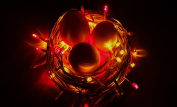 Creative conceptual photo design of Easter eggs in bird nest made with glowing colorful decoration led light bulbs and electric wire on dark black background and copy space. Close up macro top view.