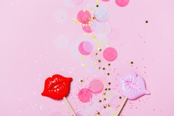 Creative confetti background with pink lips. Bright and festive. Top view, flat lay.