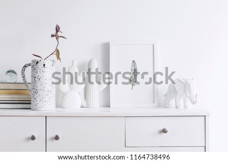 Creative cupboard with mock up poster frame, cacti, elephant figures, pink flower in stylish vase and books. Modern and minimalistic concept of shelf.