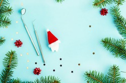creative dental christmas and new year. mirror, probe and toy tooth in santa hat on year background with fir branches