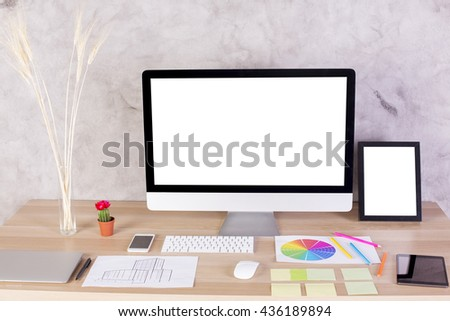 Creative designer desktop with blank white computer screen, picture frame, keyboard, laptop, wheat spikes in vase and many other items. Mock up