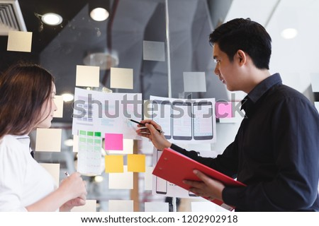 Creative designer team hands sketching of screens for mobile responsive website development with UI/UX. Developing wireframe sketch layout design mockup on smartphone screen. #1202902918