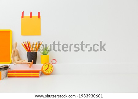 Creative desk in kids room with yellow frame mock up, plant and notebooks, note on the wall and many yellow and orange supplies.