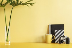 Creative desk with copy space. Empty yellow wall. Minimalistic concept.