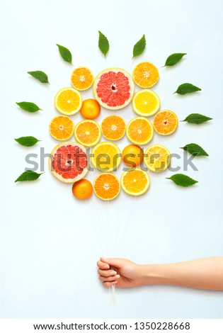 Creative diet food healthy eating concept photo of hand holding bouquet made of fresh citrus fruits full of vitamins and green leaves on white background.
