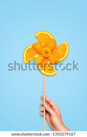 Creative diet food healthy eating concept photo of hand holding yellow toy windmill made of fresh orange slices full of vitamin on blue background. #1350279167