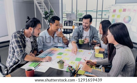 Creative director lead team brainstroming of production marketing plan to communication brand in meeting room at modern office.Diversity asian and caucasian people working togerther