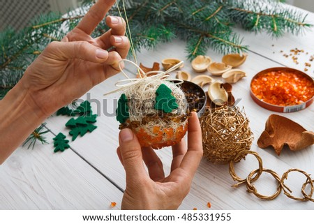 Creative diy craft hobby. Making handmade craft christmas ornaments and balls with felt spruce tree. Woman\'s leisure, holiday decorations. Closeup of female hands at white wood background