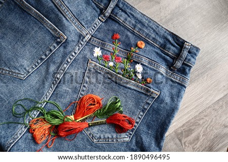 Creative DIY project, hand embroidery at home on jeans, creative hobby, clothes recycle, floral embroidery design, colorful threads, embroidery needle