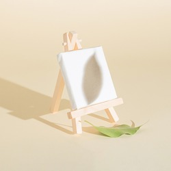 Creative easel and white canvas idea made of autumn leaf on the bright background and leaf shadow. Creative minimal concept. Painting or autumn inspiration.