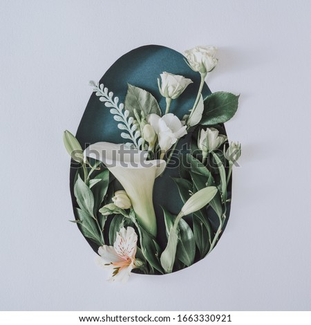 Creative Easter layout with flowers and leaves on white paper background. Spring nature Easter holiday minimal concept. Egg shape flat lay.