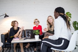 Creative female team woman collaborating, exchange phonenumbers and contacts, sharing useful information with each other, spend time together for common work.
