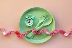 Creative flat lay composition with plate, alarm clock, spoon, fork and measuring tape on pink background. Intermittent fasting, ketogenic, diet concept.  Flat lay, copy space.